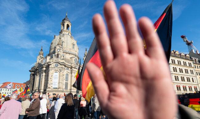 Dresden: Ein Teilnehmer einer Kundgebung von Pegida auf dem Altmarkt hält seine Hand vor die Kamera des Fotografen.