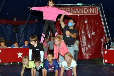Kraft und Balance ist von den Viertklässlern gefordert. Die jungen Akrobaten gestalten zusammen eine menschliche Pyramide. Zirkusdirektor Felix Kendler übt mit ihnen.