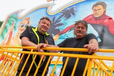 """Sie organisieren mit ihrem Team den Rummel auf dem Festplatz an der Rochlitzer Bleiche: René Schmidt (l.) und Mario Groß. Das Fahrgeschäft im Hintergrund heißt """"Sunny Beach"""" und ist eine Neuanschaffung vom Funktionstyp """"Scheibenwischer""""."""