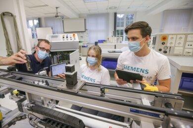Ausbilder Gerry Kebellus zeigt Lydia Kubiak und Lukas Jacob (von links), die ein duales Studium zum Berufsschulpädagogen begonnen haben, im Siemens-Bildungszentrum an der Kauffahrtei eine Schulungsanlage für Automatisierungstechnik.