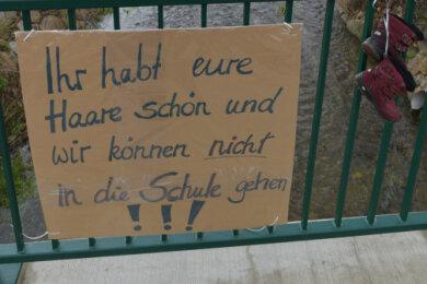 Protestplakat und Schuhe an einer Brücke in Lichtenberg.