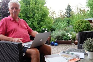 Ein Arbeitsplatz im Grünen: Ulrich Thiel, ehemaliger Leiter des Stadt-und Bergbaumuseums Freiberg, zieht mit Lektüre und Laptop gern mal in seine Oase am Haus. Einen Ruhestand gibt es für den Historiker nicht. Er forscht, schreibt und hält Vorträge, bildet sich aber auch auf Reisen weiter.