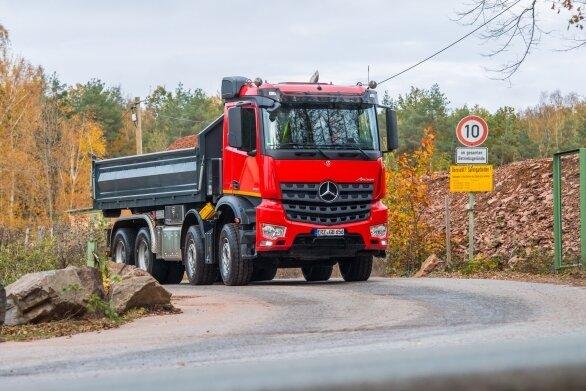 Laster, die vom Gelände kommen, tragen den roten Staub auf die Straße, die nach Leukersdorf führt.
