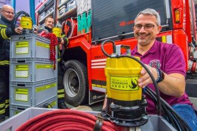 """Der Förderverein der Freiwilligen Feuerwehr Adorf hat sich mit dem Projekt """"Hilfe zur Selbsthilfe - im Hochwasserfall"""" Gedanken darum gemacht, welche Möglichkeiten es gibt, dass Einsatzkräfte und Bevölkerung im Ernstfall gleichermaßen mit zupacken können. Die Gerätewarte Tino Hofmann und Tim Ostenhausen sowie der Chef des Fördervereins der Freiwilligen Feuerwehr Adorf Marco Käbe (von links) zeigen eine der Pumpen, die für den Fall eines Hochwassers zur Verfügung gestellt werden sollen."""
