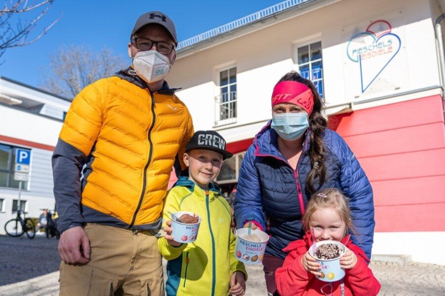 Sie gehörten am Sonntag zu den ersten Kunden an Pieschels Eisdiele in der Treuener Pfarrstraße: Christian Birner und Vicky Lenk mit Mats (8) und Leni (4) aus Schönheide mit dem gerade ergatterten Eis. Auch beim Straßenverkauf ist die Maske Pflicht, das Eis soll daheim gegessen werden.