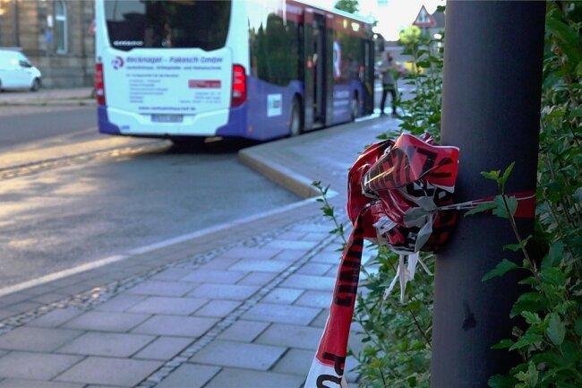 Zusammengeknotetes Absperrband der Polizei hängt noch an einem Pfahl an einer Bushaltestelle in Hof. In der Nähe wurde in der Nacht zum Dienstag ein Busfahrer tödlich verletzt.