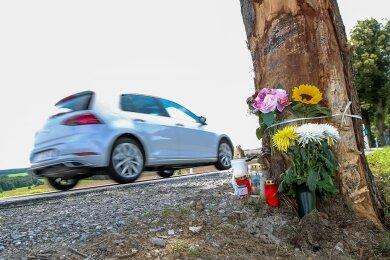 Trauernde haben Kerzen und Blumen an dem Baum hinterlassen, an dem zwei junge Männer verunglückten.