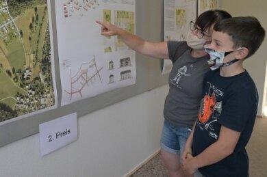 Simone Günther und ihr Sohn Hannes schauen sich die Zukunftsvisionen für die Siedlung an.