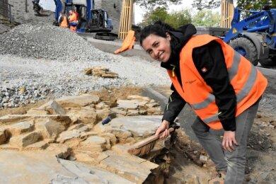 Nadine Holesch mit Resten einer Steinmauer vermutlich aus dem 14. Jahrhundert, die bei Arbeiten an der Burgauffahrt entdeckt wurde.