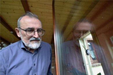 Der Mühlauer Bürgermeister Frank Petermann mit einem der Einschusslöcher in der Scheibe seiner Wintergartentür.