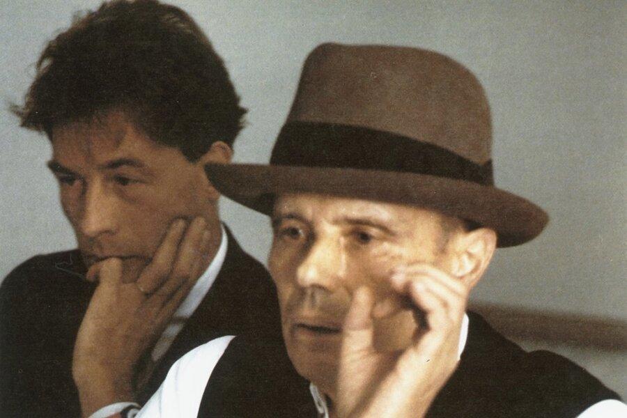 """Heiner Bastian (links) und Joseph Beuys bei einem Symposium anlässlich der Rauminstallation """"Richtkräfte einer neuen Gesellschaft"""" (1974 - 1977), Nationalgalerie Berlin, 16. März 1977."""