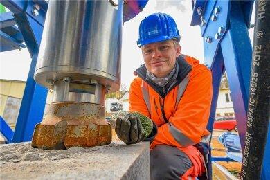 Mehrere Millimeter große Gesteinspartikel hat der Bohrhammer aus dem Granitblock gelöst. Leon Grottendieck, wissenschaftlicher Mitarbeiter am Institut für Bohrtechnik und Fluidbergbau der TU Bergakademie Freiberg, testet den Prototypen eines hydraulischen Bohrhammers für die Tiefbohrtechnik.