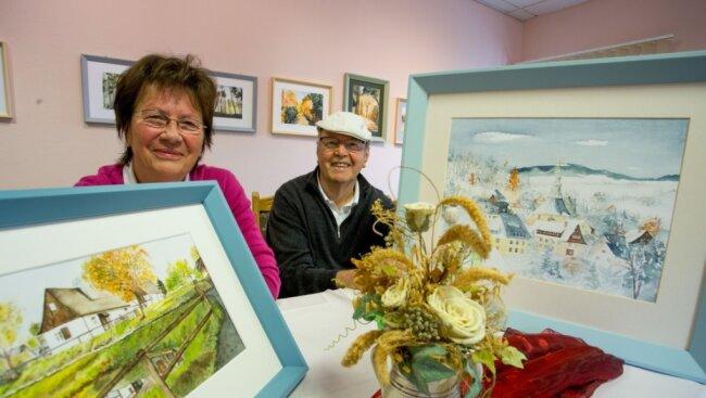 Adelheid und Reiner Lorenz mit je einem ihrer Bilder. Die beiden Seiffener Eheleute stellen derzeit gemeinsam im Rothenthaler Haus der Begegnung aus.