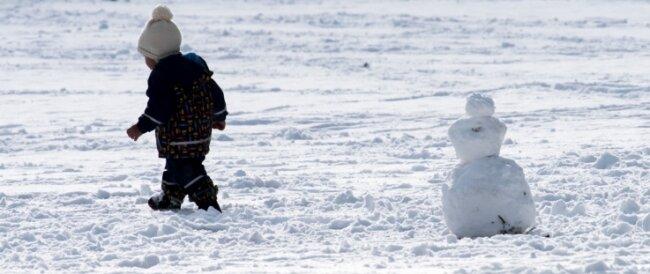 Ein Kind hat einen kleinen Schneemann gebaut.