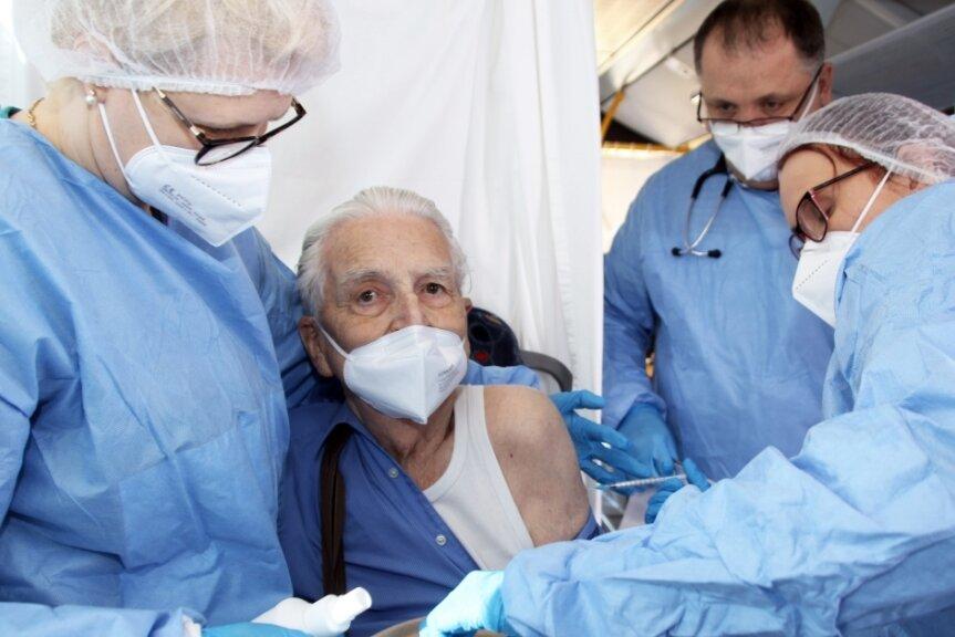 Bernadette Laub gibt dem 92-jährigen Heinz Schmieder Unterstützung, Dr. Peter Laub passt auf und Annett Göbel(v. l.) setzt die Spritze.