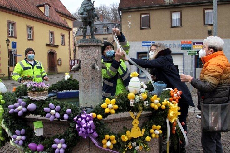 In Lunzenau schmückten Heimatfreundinnen und Bauhofmitarbeiter den Marktbrunnen mit einer Osterkrone.