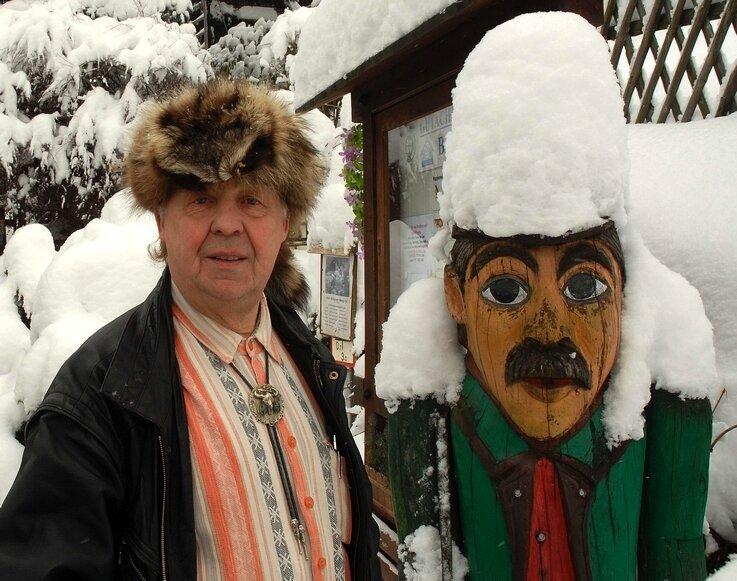 Zwei Scharfensteiner mit Mütze: Helmar Bauer und eine Figur des Karl Stülpner vor seinem Haus unterhalb der Burg.