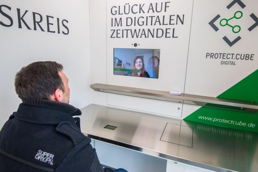 Landratsamts-Mitarbeiterin Sindy Seidel berät über einen Monitor in der Besuchsbox testweise einen Gast. An und auf dem Tisch sind ein Scanner sowie ein Drucker angebracht.