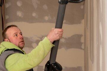 Michael Rose verschleift eine Wand im Bühnenbereich.