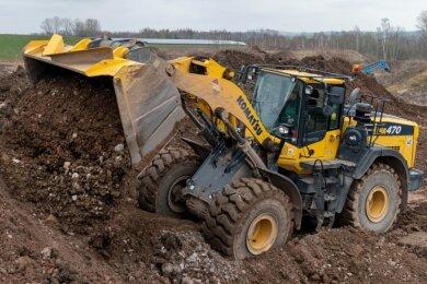 Mit schwerer Technik wird das Füllmaterial in der Grube verteilt und anschließend verdichtet.