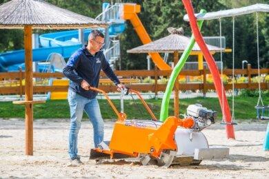 Badbetreiber Carsten Dietzsch säubert den Sand der Volleyballanlage.