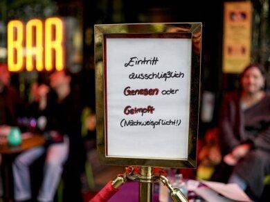 Vor einer Bar im Hamburger Stadtteil St. Georg steht ein Hinweisschild, welches auf den Einlass nach der 2G-Regel hinweist.