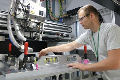 Produktionsleiter Sven Böhme richtet bei der Firma JT Energy Systems im Gewerbegebiet Ost in Freiberg den Laserschweißer für die Produktion von Lithium-Ionen-Zellpacks ein.