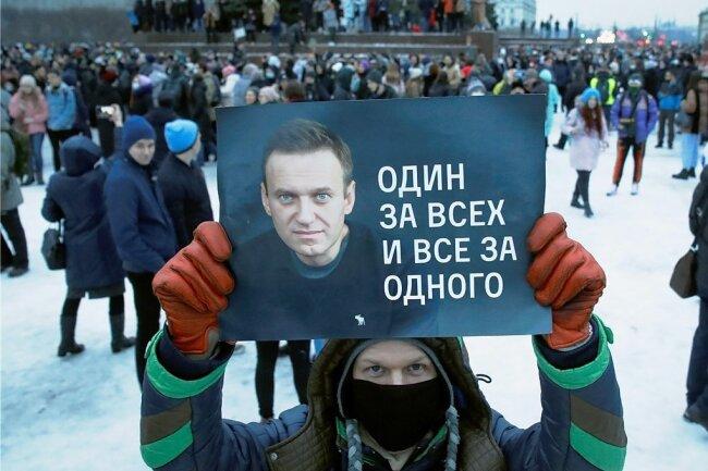 """Ein Mann hält in St. Petersburg ein Plakat mit einem Porträt Alexej Nawalnys und der Aufschrift """"Einer für alle und alle für einen"""", während er an einer Protestkundgebung gegen die Inhaftierung des Oppositionsführers teilnimmt."""