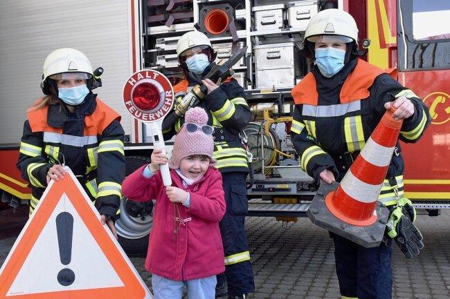 In Lichtenwalde verstärken vier Frauen das Team der Feuerwehr. Zu ihnen zählen Franziska Heller (li.), Peggy Rantzsch und Anett Barth (r.), die mit ihrem Einsatzwerkzeug umgehen und auch das Löschfahrzeug fahren können. Zum Fototermin verstärkt die vierjährige Paula die Gruppe.