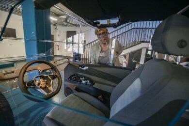 Das Schnittmodell eines Elektroautos ID.3 von Volkswagen zeigt, wie viele textile Fasern beim Bau verwendet werden, etwa in den Rädern und dem Lenkrad. Hinten: die wissenschaftliche Mitarbeiterin Anett Polig.