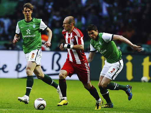 Bayerns Torschütze Arjen Robben setzt sich gegen zwei Bremer durch