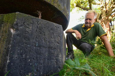 Anwohner Stefan Tetzner in seinem Garten mit einem Teil des früheren Obelisken, der auf dem Beutenberg stand. Darauf sind noch eingeritzte Initialen und Jahreszahlen zu erkennen. Die ältesten stammen von 1887.