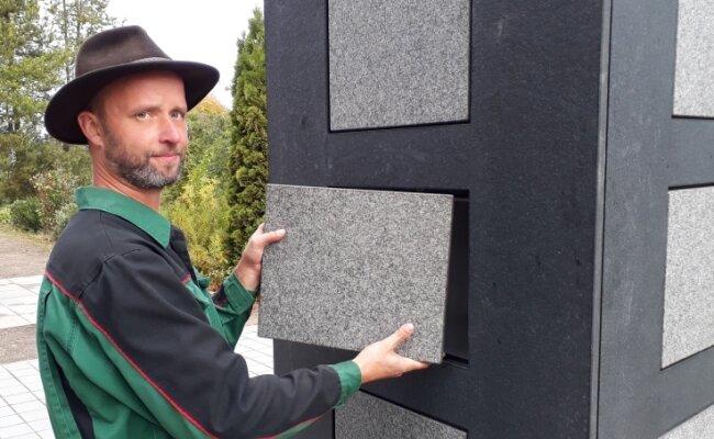 Bei der Indienststellung des Kolumbariums auf dem Zentralfriedhof im Oktober 2018 zeigte Friedhofsgärtner Marcus Hüllenhagen, wie die Nischen in den Stelen mit Granitplatten verschlossen werden.
