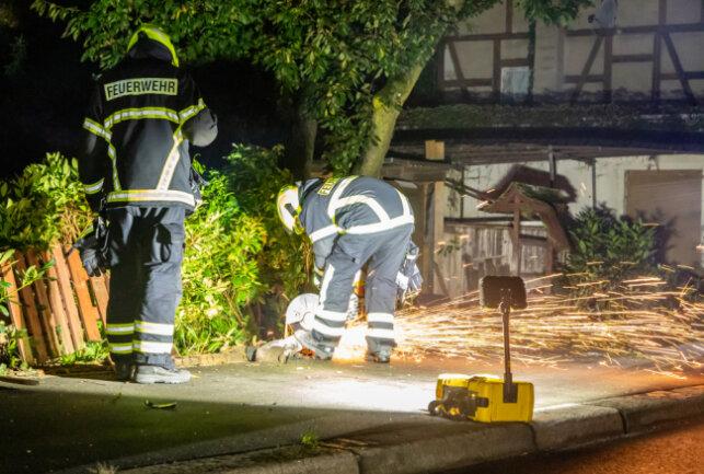 Kameraden der Feuerwehr demontieren die Straßenlaterne mit einem Trennschleifer
