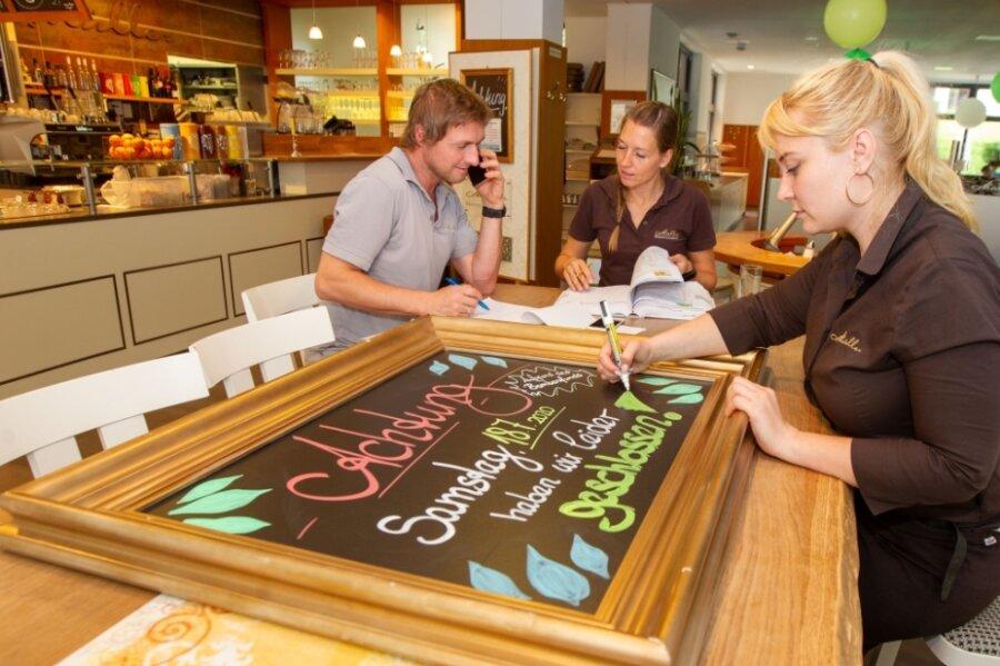 Den Inhabern der Bäckerei Müller, Rico und Antje Wagner, bleibt nichts anderes übrig, als vorsorglich ihre Läden in der Innenstadt zu schließen. Mitarbeiterin Claudia Pflug schreibt das Hinweisschild für die Kunden.