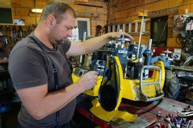 Lars Seifert in seiner Werkstatt am Staffelweg bei Reparaturarbeiten an einem Mähroboter.