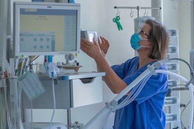 Eine Krankenschwester prüft ein Beatmungsgerät in einem Zimmer einer Intensivstation.