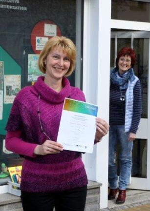 Die Vereinsvorsitzende Jana Weber (vorn) und die Stadtteilmanagerin Sabine Resche zeigen die Siegerurkunde des Ideenwettbewerbs.