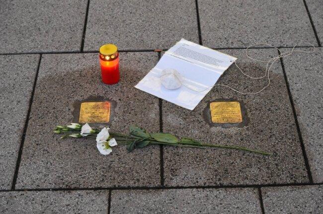 Blumen und ein Grablicht vor zwei Stolpersteinen.