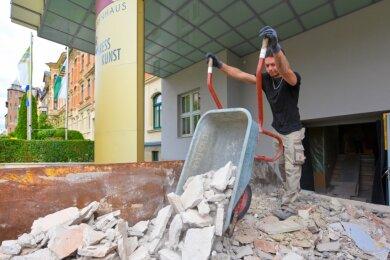 Tobias Klug entsorgt Bauschutt, der beim Schaffen des Durchbruchs für den Aufzugschacht in der Kassenhalle des Neuberinhauses anfällt.