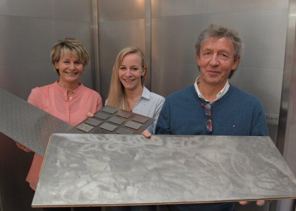 Volker Queck (rechts) zeigt die allererste Edelstahl-Bodenplatte, mit der er zu experimentieren anfing. Seine Frau Katrin (links) hält eines der inzwischen patentierten Paneele, Tochter Josefine präsentiert die zwölf derzeit verfügbaren Oberflächen-Varianten. Im Hintergrund eine Wand aus Queck-Edelstahl-Segmenten.