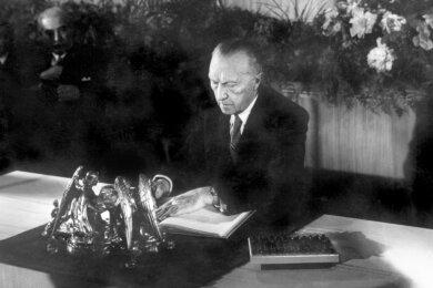 Bedeutender Moment: Der Präsident des Parlamentarischen Rates, Konrad Adenauer, bei der Unterzeichnung des Grundgesetzes am 23. Mai 1949.