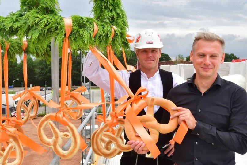 Polier Marco Gerlach und Dirk Schäfer, Chef von Schäfers Bäckerei, bereiten den Richtkranz vor.
