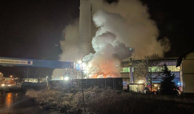 Während der Löscharbeiten der Feuerwehr türmten sich große Wolken aus Dampf in den Himmel. Auf dem Werksgelände der Nickelhütte Aue waren im Freien alte Autobatterien in Brand geraten.