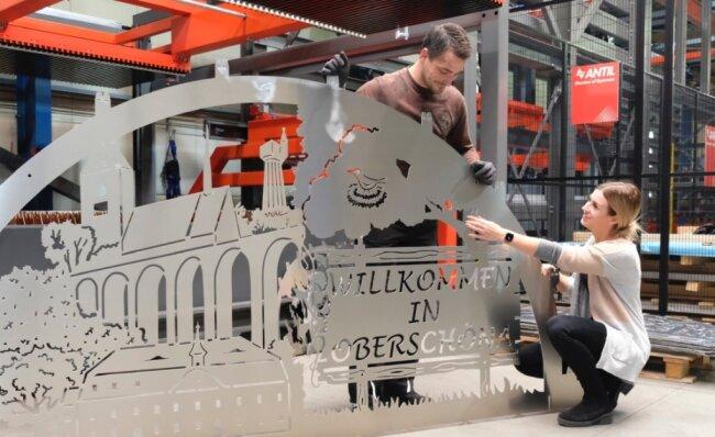 Lara Jakob vom Weber-Marketing und Mitarbeiter Toni Herrmann mit dem XXL-Willkommensgruß von Oberschöna bei Freiberg. Der an einer neuen Laserschneidanlage gefertigte Hingucker aus Alu wird nun wie alle Bögen, Lichterspitzen, Baumschmuck oder Teelichthalter im Lackierzentrum Reichenbach pulverbeschichtet.