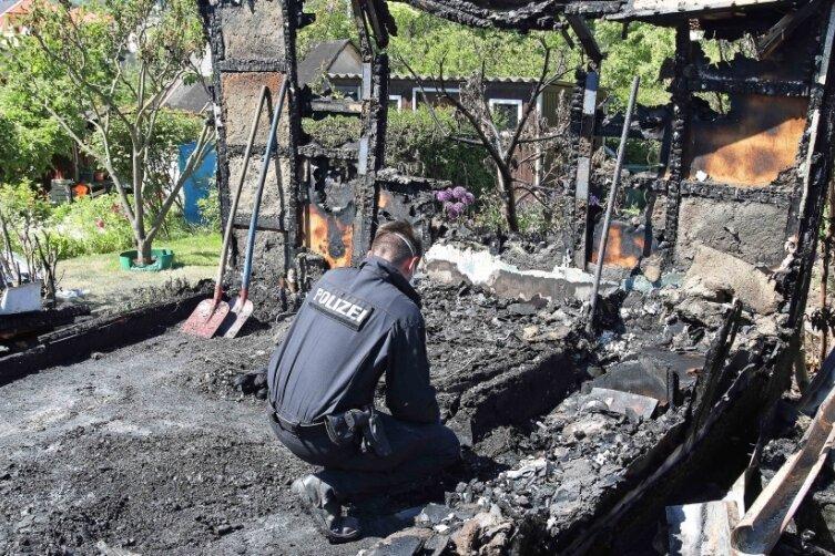 """Ein fast schon gewohntes Bild im Frühjahr in Crimmitschau: Ermittler suchen wie hier in der Kleingartanlage """"Am Höllgraben"""" nach Hinweisen zur Brandursache."""