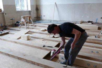 Nach reiflicher Überlegung wurde ein geeignetes Holzbalkenverbundsystem für den Boden gefunden. Es wird mit Beton verfüllt und wird am Ende mit Kunststoff als Bodenbelag versehen.