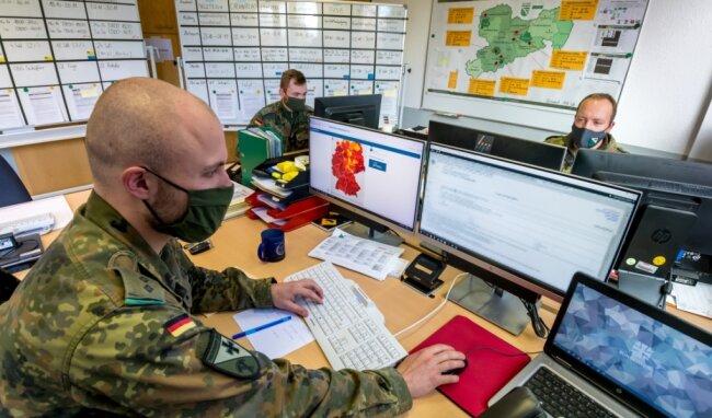 Ein Blick in die Operationszentrale Covid-19 der Erzgebirgskaserne: Oberleutnant Max Jackisch, Oberleutnant Robert-Helge Patry und Hauptmann Robin Satzke (v. l.) gehören zu dem siebenköpfigen Team, das sieben Tage in der Woche die Corona-Einsätze steuert.