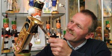 """<p class=""""artikelinhalt"""">Museumsinhaber Uwe Löschner baut die Sonderausstellung mit geschnitzten Bergmannsnussknackern auf. </p>"""