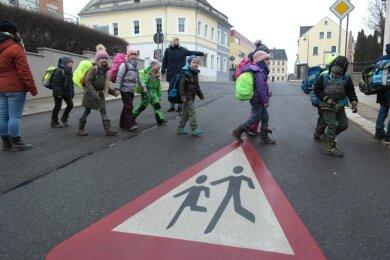"""Zwar wurden großflächige Piktogramme auf die Fahrbahn aufgebracht und mit """"Achtung Kinder"""" auf die nahe Schule aufmerksam gemacht. Gerast wird an der Bahnhofstraße bislang unverdrossen."""